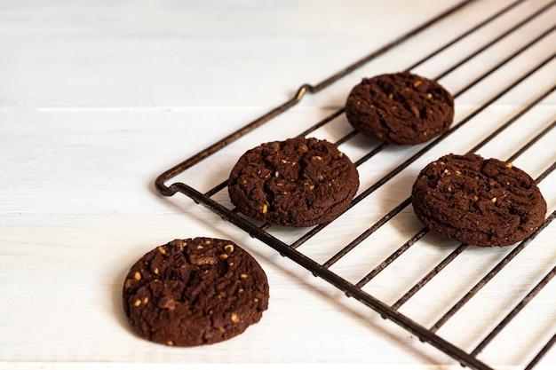 Zelfgemaakte amerikaanse chocoladekoekjes met noten op een grill op witte houten achtergrond. vers gebak.