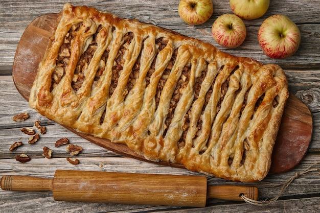 Zelfgemaakte appel- en walnoottaart op een houten bord, omringd door ingrediënten op een ruwe houten tafel. thuis eten