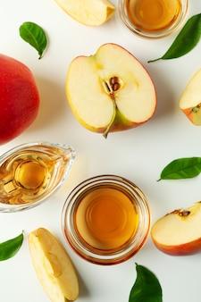Zelfgemaakte appelazijn en ingrediënten op wit