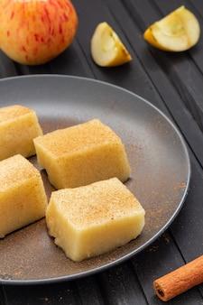 Zelfgemaakte appelgelei vierkanten met kaneel op zwarte tafel