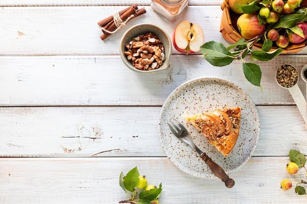 Zelfgemaakte appeltaart en ingrediënten op een witte houten achtergrond. bovenaanzicht. kopieer ruimte