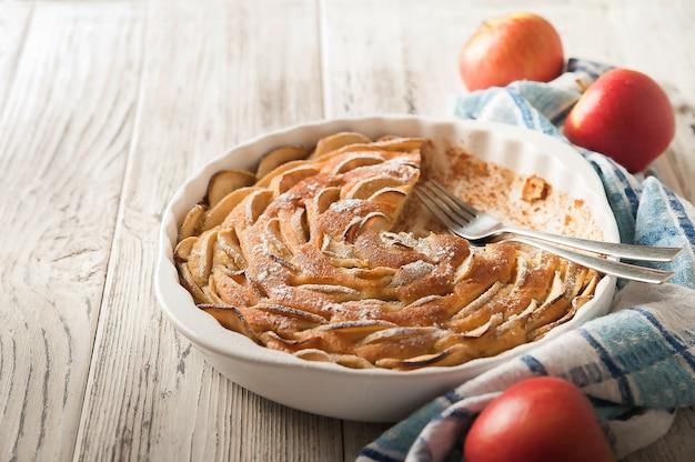 Zelfgemaakte appeltaart op een wit hout bij het raam