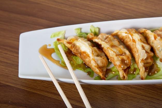 Zelfgemaakte aziatische kip gyozas met sojasaus.