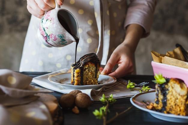 Zelfgemaakte bananencake gieten met warme vloeibare chocolade