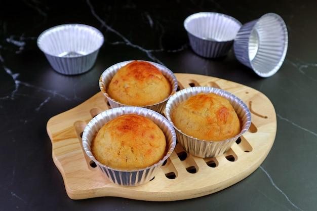 Zelfgemaakte bananenmuffins in vorm op houten broodplank met lege aluminium muffinvorm op zwart marmeren tafel in de keuken