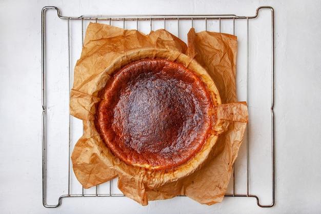 Zelfgemaakte baskische gebrande cheesecake direct na het bakken op een rooster.