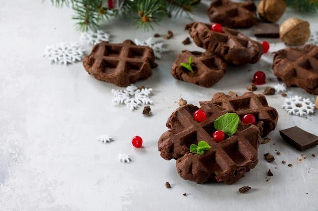 Zelfgemaakte belgische chocoladewafels met verse bessen en munt op een grijze steen met kopieerruimte