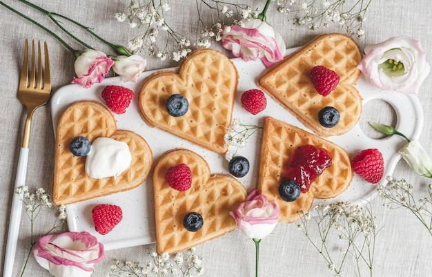 Zelfgemaakte belgische hartwafels met aardbeiensaus en bessen