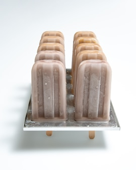 Zelfgemaakte biologische chocolade-ijs lollie in plastic vormen met een weerspiegeling van schaduwen op een witte achtergrond met kopie ruimte.
