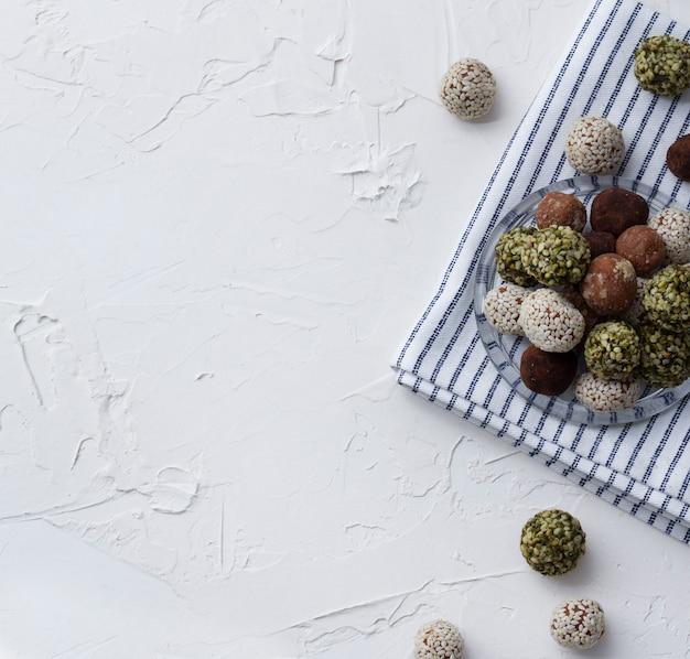 Zelfgemaakte biologische gezonde rauwe energie zoete ballen op een plaat met een servet.