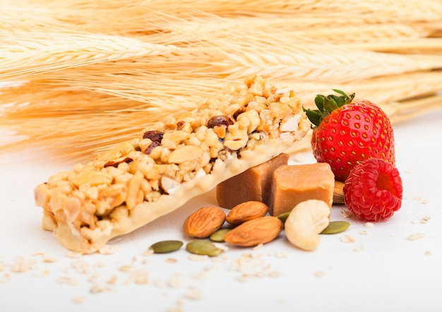 Zelfgemaakte biologische granola mueslireep met noten en gedroogd fruit op wit met haver en rauwe tarwe. aardbei en framboos en karamel.