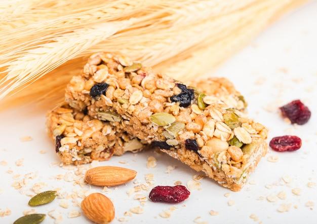 Zelfgemaakte biologische granola mueslireep met noten en gedroogd fruit op wit met haver en rauwe tarwe.