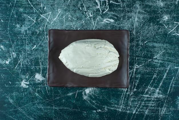 Zelfgemaakte biologische kaas op een houten schotel. hoge kwaliteit foto