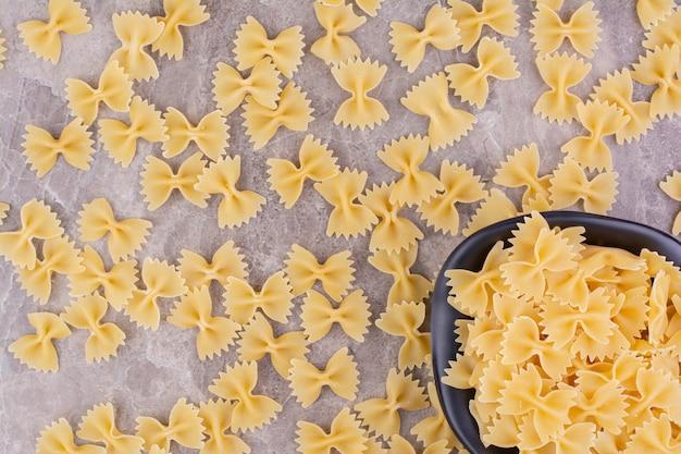 Zelfgemaakte biologische pasta's in een zwarte keramische plaat