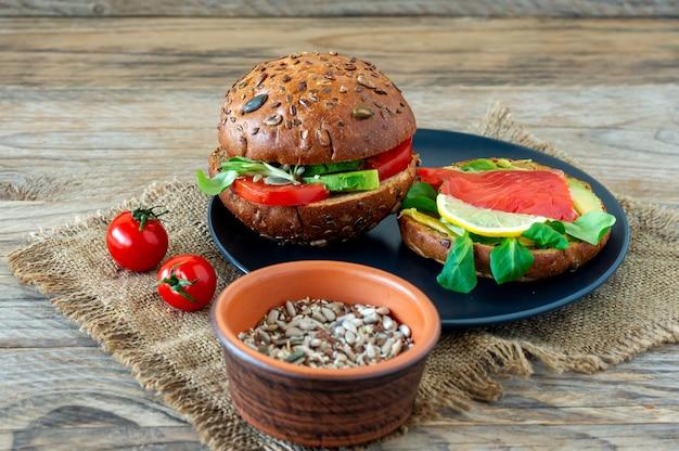 Zelfgemaakte biologische zalmburger met tomaat, veldsla en avocado op een bord op houten achtergrondkleur. gezonde biologische voeding.