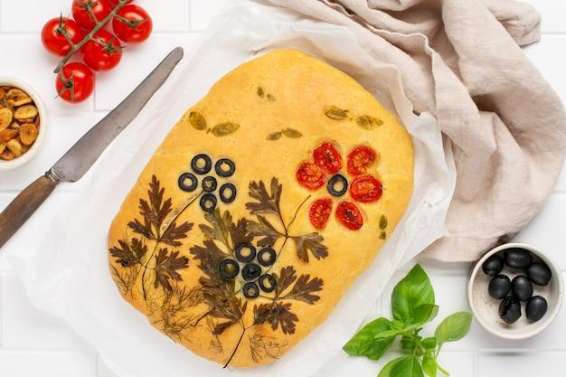 Zelfgemaakte bloemfocaccia. creatief idee van focaccia-koken. knapperige focaccia met groenten. bovenaanzicht.