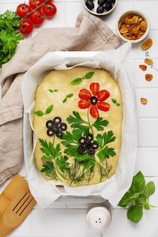 Zelfgemaakte bloemfocaccia. rauwe focaccia creatief versierd met groenten op perkamentpapier. zuurdesem deeg. versierd italiaans brood. bovenaanzicht.