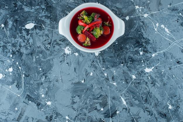 Zelfgemaakte borsjt soep in een kom, op de blauwe achtergrond.