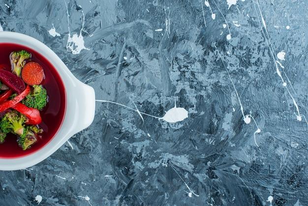 Zelfgemaakte borsjt soep in een kom op het blauwe oppervlak