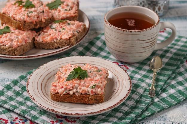 Zelfgemaakte broodjes met krabstokken, kaas en wortelen op een bord op een geruit tafelkleed, horizontale oriëntatie