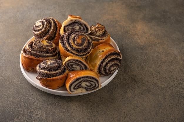 Zelfgemaakte broodjes met maanzaad op een witte plaat op een donkere achtergrond close-up.