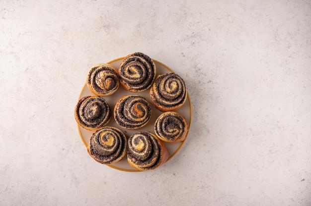 Zelfgemaakte broodjes met maanzaad op een witte plaat op een lichte achtergrond bovenaanzicht.