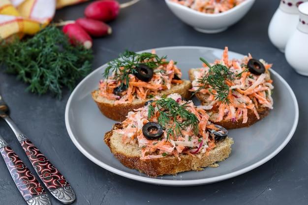 Zelfgemaakte broodjes met wortelen en radijs, versierd met gekookt ei en zwarte olijven in een bord tegen een donkere