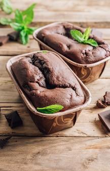 Zelfgemaakte brownies met donkere chocolade en munt op een rustieke houten achtergrond. kleine geportioneerde ovenschaal. selectieve aandacht. verticale foto
