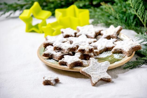 Zelfgemaakte cacao-amandelkoekjes in stervorm met wit glazuur en poedersuiker. op keramische plaat met kerststerren koekjesmessen, thuja takken, decoraties over wit tafelkleed. kopieer ruimte