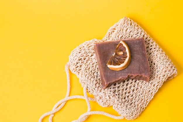 Zelfgemaakte cacaozeep op een gebreid washandje met een plakje gedroogde sinaasappel op een geel oppervlak