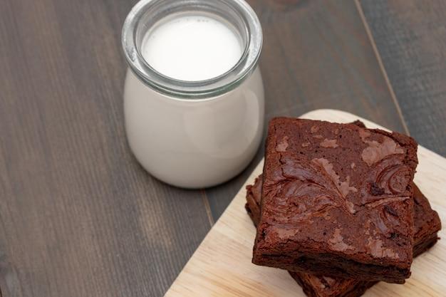 Zelfgemaakte cake chocolade brownies en melk op houten tafel