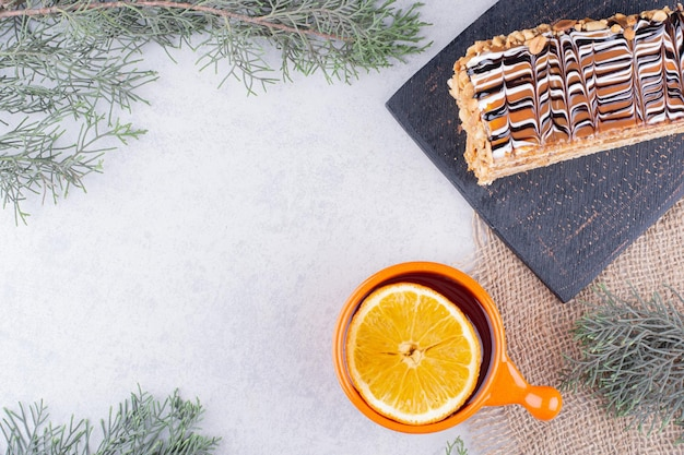 Zelfgemaakte cake en kopje thee op marmeren oppervlak.