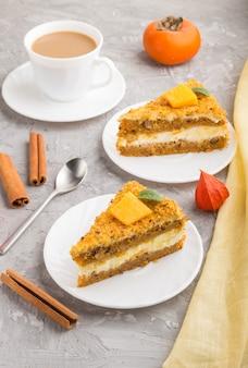 Zelfgemaakte cake met kaki en pompoen en een kopje koffie op een grijze betonnen ondergrond met geel textiel