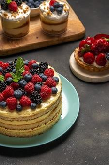 Zelfgemaakte cake met verse bessen en zoete desserts op donker.