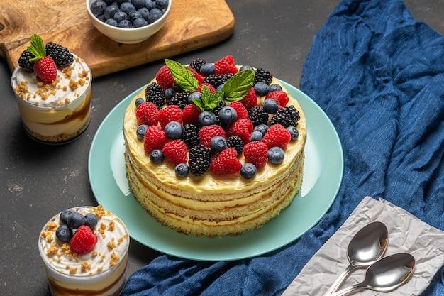 Zelfgemaakte cake met verse bessen en zoete desserts op donkere achtergrond.