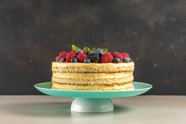 Zelfgemaakte cake met verse bessen op donkere achtergrond.