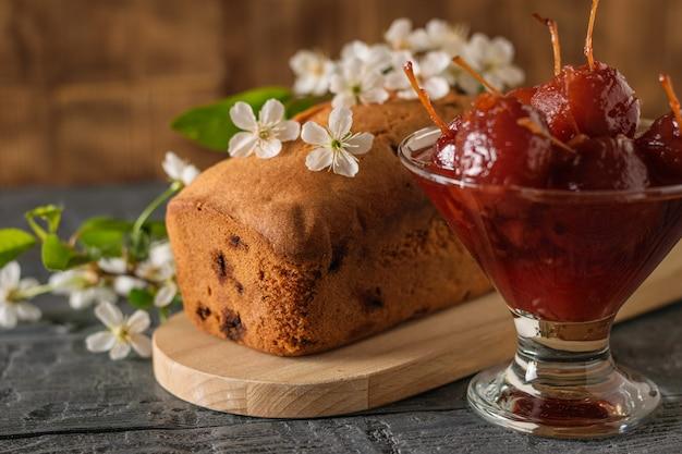 Zelfgemaakte cake versierd met kersenbloemen en appeljam op tafel. zelfgemaakte zoetigheden volgens oude recepten.