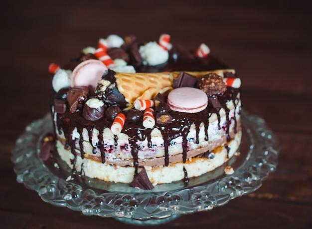 Zelfgemaakte cake versierd met snoepjes, macaroonndwafels.