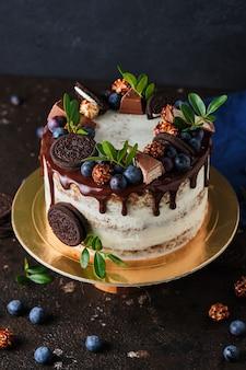Zelfgemaakte cake voor de vakantie met roomkaasroom, versierd met chocoladekoekjes en bessen.