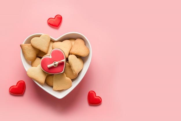 Zelfgemaakte cake voor valentijnsdag. hartvormige koekjes in plaat op roze. uitzicht van boven.