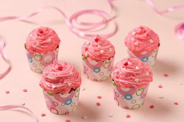 Zelfgemaakte cakejes met room op een roze achtergrond.