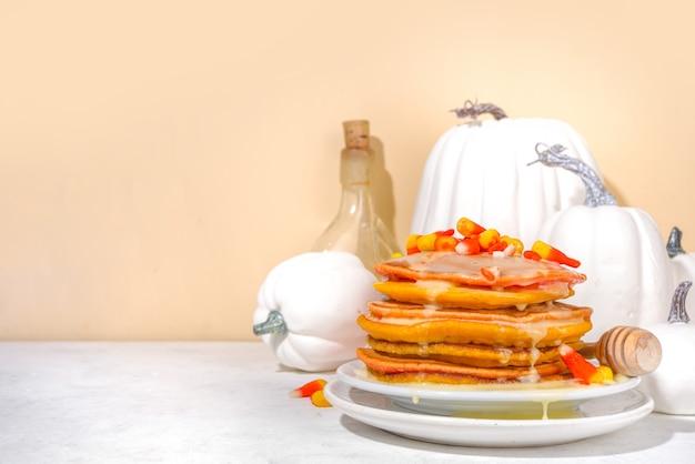 Zelfgemaakte candy corn pannenkoeken. stapel gele en oranje pannenkoeken met zoete saus en traditionele halloween-snoepjes met snoepkoord
