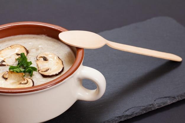 Zelfgemaakte champignonroomsoep in porseleinen kom met gesneden champignons op een zwarte stenen bord. bovenaanzicht.