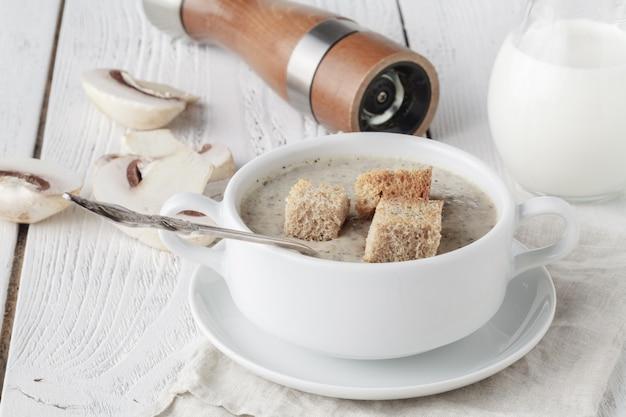 Zelfgemaakte champignonroomsoep op de houten tafel