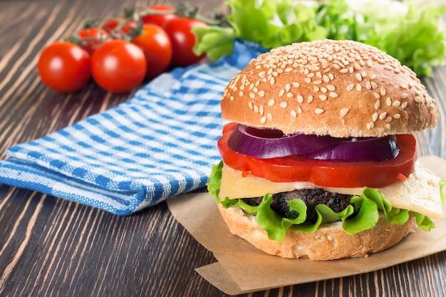 Zelfgemaakte cheeseburger met runderpasteitjes en verse salade op seasame-broodjes, gesered op bruine houten tafel.