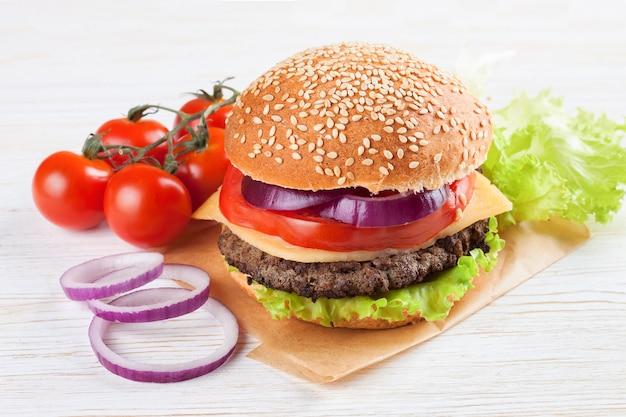 Zelfgemaakte cheeseburger met rundvleespasteitjes, verse salade, tomaten en ui op seasame-broodjes, geserveerd op witte houten tafel.