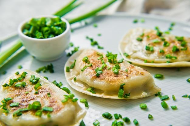 Zelfgemaakte chinese dumplings, eetstokjes, verse groene uien.