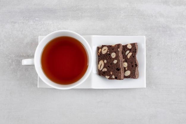 Zelfgemaakte chocolade brownies en een kopje thee op een schotel, op de marmeren tafel.