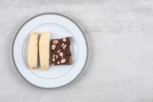 Zelfgemaakte chocolade brownies en koekje op een bord, op de marmeren tafel.