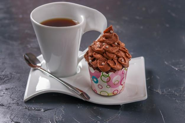 Zelfgemaakte chocolade cupcake met room en een kopje koffie gerangschikt op een donkere ondergrond, close-up, horizontale oriëntatie
